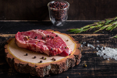 Raw meat steak on dark wooden background ready to roasting