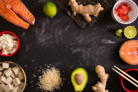Overhead shot of ingredients for sushi on dark background. Raw salmon steak, rice, cream cheese, avocado, lime, pickled ginger (gari), raw ginger, wasabi, soy sauce, nori, сhopsticks. Asian food background. Space for text Stock Photo
