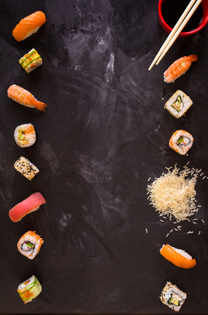 Overhead shot of sushi on dark background. Sushi rolls, nigiri, rice, soy sauce, �hopsticks. Asian food background. Space for text. Sushi set Foto de archivo