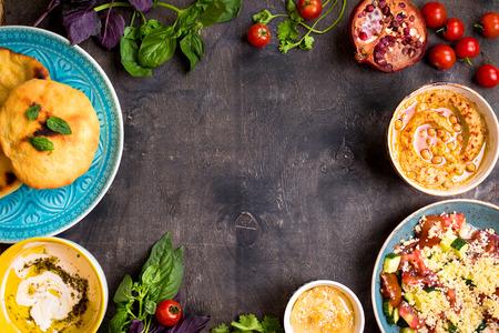 ensalada: Mesa servida con platos vegetarianos tradicionales de oriente medio. Hummus, tahini, pitta, ensalada de cuscús y dip de suero de leche con aceite de oliva. Cena