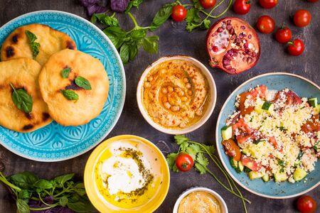ensalada: Mesa servida con platos vegetarianos tradicionales de oriente medio. Hummus, tahini, pitta, ensalada de cusc�s y dip de suero de leche con aceite de oliva. Cena