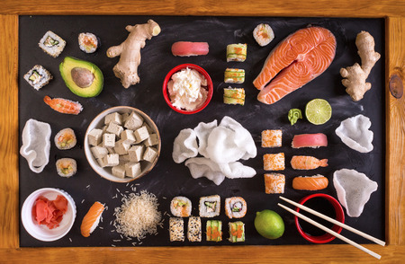Set of traditional japanese food on a dark background. Sushi rolls, nigiri, raw salmon steak, rice, cream cheese, avocado, lime, pickled ginger (gari), raw ginger, wasabi, soy sauce, nori, �hopsticks. Asian food frame. Dinner party. Space for text Stockfoto