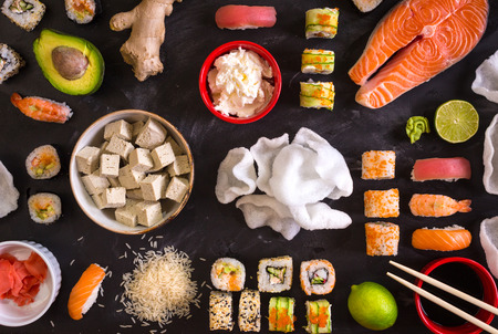 Set of traditional japanese food on a dark background. Sushi rolls, nigiri, raw salmon steak, rice, cream cheese, avocado, lime, pickled ginger (gari), raw ginger, wasabi, soy sauce, nori, сhopsticks. Asian food frame. Dinner party. Space for text
