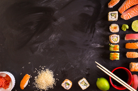 Overhead shot of sushi and ingredients on dark background. Sushi rolls, nigiri, raw salmon steak, rice, cream cheese, avocado, lime, pickled ginger (gari), raw ginger, wasabi, soy sauce, nori, сhopsticks. Asian food background. Space for text