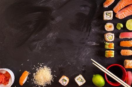 fish and chips: Tiro de arriba de sushi y los ingredientes en el fondo oscuro. Rollos de sushi, nigiri, filete crudo salmón, arroz, queso crema, aguacate, limón, jengibre encurtido (Gari), jengibre crudo, wasabi, salsa de soya, nori, ?hopsticks. Fondo de la comida asiática. Espacio para el texto Foto de archivo