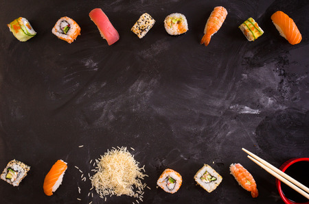 Overhead shot of sushi on dark background. Sushi rolls, nigiri, rice, soy sauce, сhopsticks. Asian food background. Space for text. Sushi set 스톡 콘텐츠