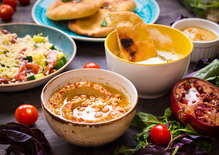 Table served with middle eastern traditional vegetarian dishes. Hummus, tahini, pitta, couscous salad and buttermilk dip with olive oil. Dinner party