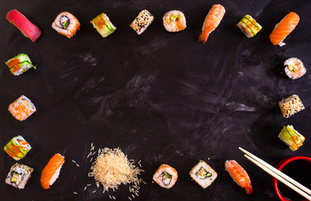 Overhead shot of sushi on dark background. Sushi rolls, nigiri, rice, soy sauce, �hopsticks. Asian food background. Space for text. Sushi set Banque d'images