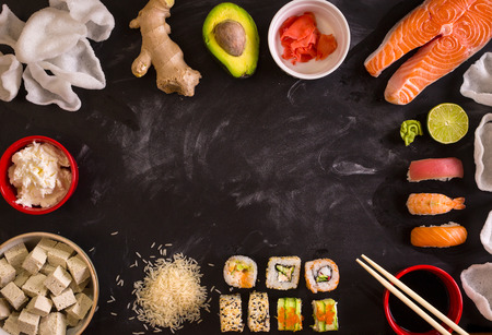 Overhead shot of sushi and ingredients on dark background. Sushi rolls, nigiri, raw salmon steak, rice, cream cheese, avocado, lime, pickled ginger (gari), raw ginger, wasabi, soy sauce, nori, �hopsticks. Asian food background. Space for text