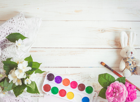 Desk of creative worker. Paints, brush and flowers. Top view background Foto de archivo