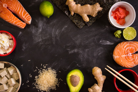sushi restaurant: Overhead shot of ingredients for sushi on dark background. Raw salmon steak, rice, cream cheese, avocado, lime, pickled ginger (gari), raw ginger, wasabi, soy sauce, nori, сhopsticks. Asian food background. Space for text