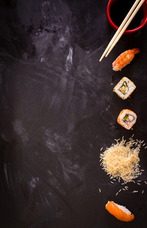 Overhead shot of sushi on dark background. Sushi rolls, nigiri, rice, soy sauce, сhopsticks. Asian food background. Space for text. Sushi set Stock Photo