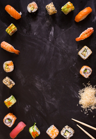 Overhead shot of sushi on dark background. Sushi rolls, nigiri, rice, soy sauce, �hopsticks. Asian food background. Space for text. Sushi set Banco de Imagens