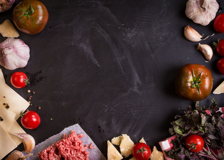 Set of ingredients for italian lasagne. Black food background with free space for text. Pasta, tomatoes, fresh ground meat, parmesan, mozzarella, basil, garlic on a rustic chalkboard. Overhead