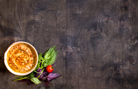 plate setting: Hummus on a plate with cherry tomatoes and herbs on a dark wooden background. Middle eastern dish. Space for text