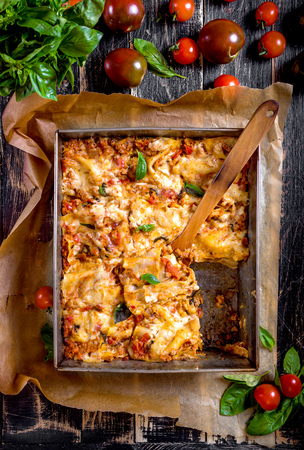 Top view of a delicious traditional italian lasagna made with minced beef bolognese sauce topped with basil leafs served on a rustic dark wooden table Foto de archivo