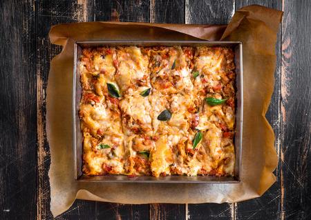다진 쇠고기 그레고리력 소스로 만든 맛있는 전통적인 이탈리아 라자 냐의 상위 뷰는 소박한 어두운 나무 테이블에 봉사 바질 잎을 얹어