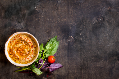 Hummus on a plate with cherry tomatoes and herbs on a dark wooden background. Middle eastern dish. Space for text