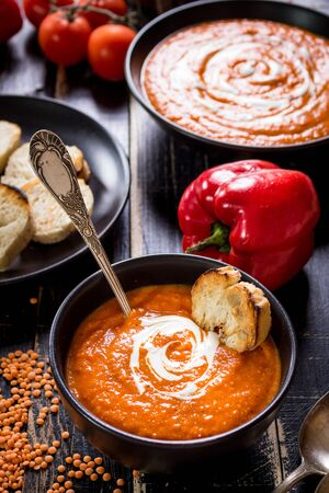 pumpkin soup: Delicious pumpkin soup with heavy cream on dark rustic wooden table with red bell pepper, bread toasts, lentil, tomatoes