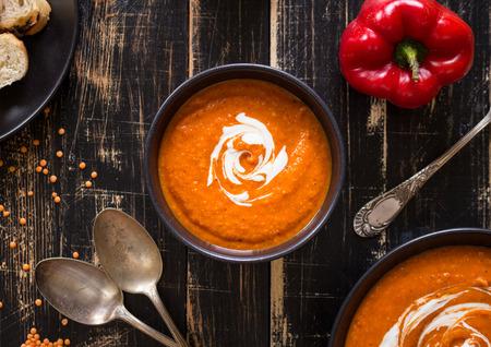 madera r�stica: Deliciosa sopa de calabaza con crema de leche en la mesa de madera r�stica oscuro con pimiento rojo, tostadas de pan, lentejas. Vista superior