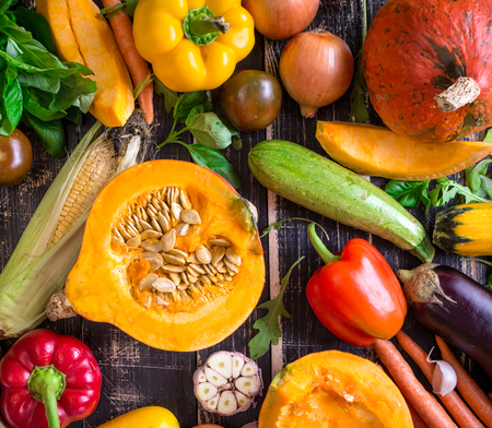 Close up of fresh vegetables on a old rustic dark textured table. Autumn background. Healthy eating. Sliced pumpkin, zucchini, squash, bell peppers, carrots, onions, cut garlic, tomatoes, eggplant, corn cob, rucola and basil. Top view Foto de archivo