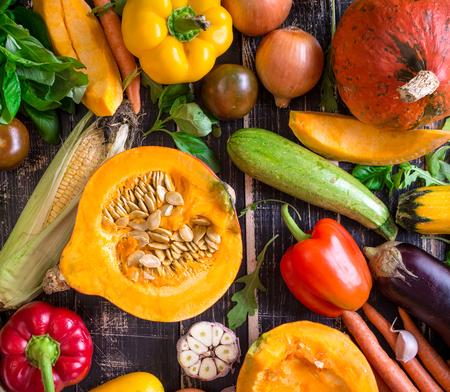 ajos: Primer plano de las verduras frescas en una mesa con textura de edad oscura r�stico. Fondo del oto�o. Alimentaci�n saludable. Calabaza rebanada, calabac�n, calabaza, pimientos, zanahorias, cebollas, ajo cortado, tomates, berenjenas, mazorca de ma�z, r�cula y albahaca. Vista superior