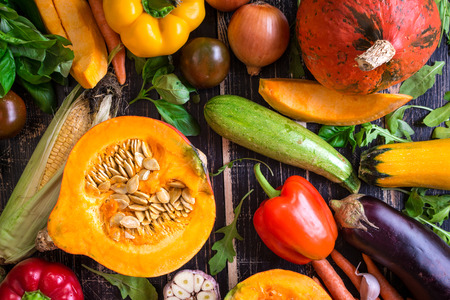ingredient: Fresh vegetables scattered on a old rustic dark textured table. Autumn background. Healthy eating. Sliced pumpkin, zucchini, squash, bell peppers, carrots, onions, cut garlic, tomatoes, eggplant, corn cob, rucola and basil. Top view