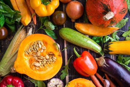 zanahoria: Las verduras frescas esparcidos sobre una mesa con textura oscura rústico de edad. Fondo del otoño. Alimentación saludable. Calabaza rebanada, calabacín, calabaza, pimientos, zanahorias, cebollas, ajo cortado, tomates, berenjenas, mazorca de maíz, rúcula y albahaca. Vista superior Foto de archivo