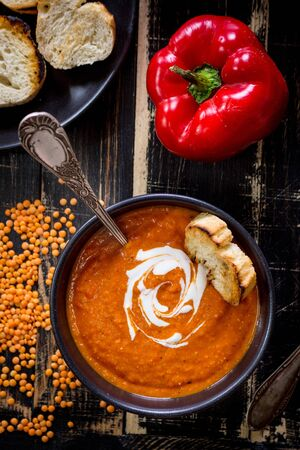 Delicious pumpkin soup with heavy cream on dark rustic wooden table with red bell pepper, bread toasts, lentil. Top view