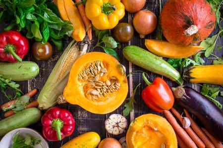 Verse groenten verspreid over een oude rustieke donkere structuur tafel. Herfst achtergrond. Gezond eten. Gesneden pompoen, courgette, squash, paprika, wortelen, uien, gesneden knoflook, tomaten, aubergines, maïskolf, rucola en basilicum. Bovenaanzicht