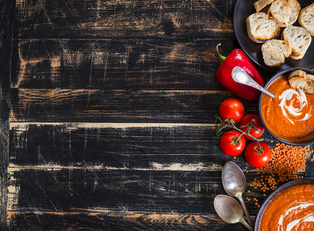 to black: Delicious pumpkin soup with heavy cream on dark rustic wooden table with red bell pepper, toasts. AutumnHalloweenThanksgiving day background. Top view. Space for text Stock Photo