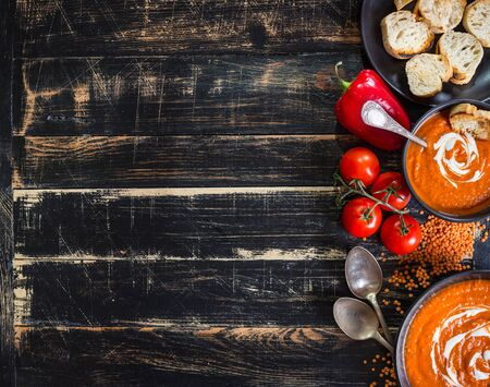 tomate: Delicious pumpkin soup with heavy cream on dark rustic wooden table with red bell pepper, toasts. AutumnHalloweenThanksgiving day background. Top view. Space for text Banque d'images