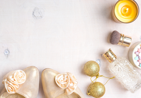 christmas perfume: Cosmetic objects frame with gold heels, gold glitter christmas balls, perfume bottle, burning candle, meteorites powder and brush.