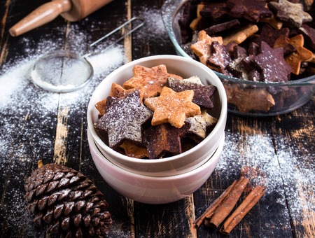chocolate biscuit: Assorted christmas ginger cookies on plate with cinnamon sticks, pinecones over dark wooden table.