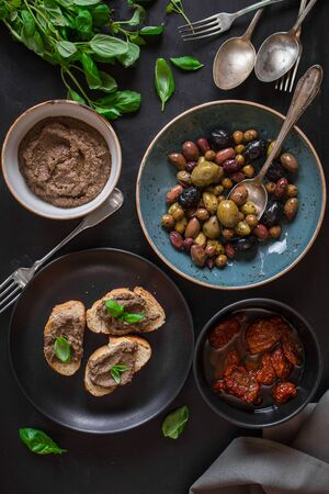 antipasto platter: Table served with bread, tapenade, assorted olives, dried tomatoes in olive oil and basil. Dinner table with french provence appetizers and canapes