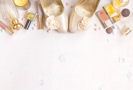 meteorites: Cosmetic objects frame with gold heels, gold glitter nail polish, perfume bottle, candle, blush, lip gloss, brushes.