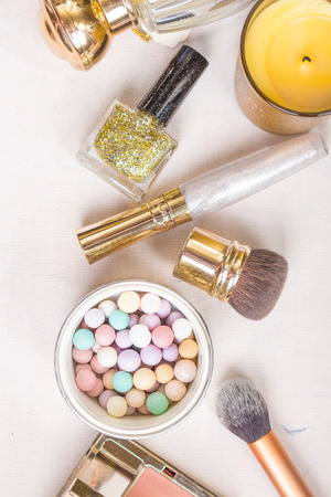 meteorites: Glamour chic cosmetic set in golden colour. Cosmetic objects: gold heels, gold glitter nail polish, perfume bottle, meteorites, blush, lip gloss, brushes. Getting ready for a party Stock Photo