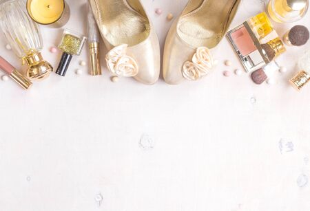 meteorites: Cosmetic objects frame with gold heels, gold glitter nail polish, perfume bottle, meteorites, blush, lip gloss, brushes. Stock Photo