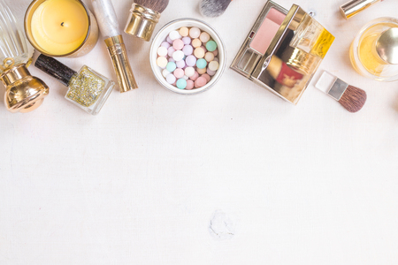 meteorites: Glamour chic cosmetic background in golden colour. Cosmetic objects frame with gold heels, gold glitter nail polish, perfume bottle, meteorites, blush, lip gloss, brushes. Getting ready for a party