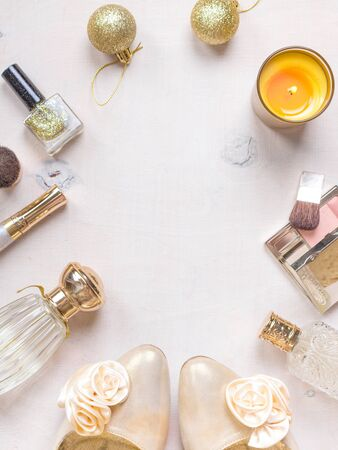 christmas perfume: Cosmetic objects frame with gold heels, christmas balls, gold glitter nail polish, perfume bottle, burning candles, blush, lip gloss, brushes.