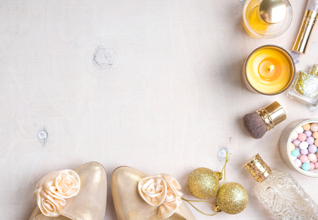 fragrance: Cosmetic objects frame with gold heels, christmas balls, gold glitter nail polish, perfume bottle, burning candles, blush, lip gloss, brushes.
