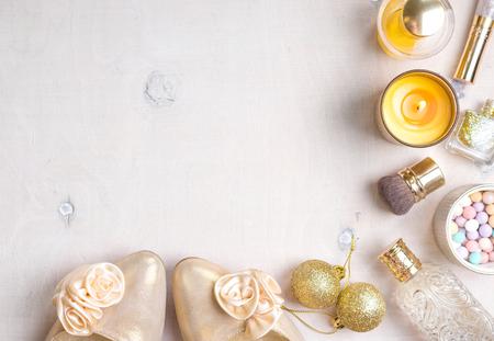 Marco de objetos cosmética con tacones de oro, bolas de Navidad, brillo esmalte de uñas de oro, botella de perfume, velas encendidas, rubor, brillo de labios, pinceles.