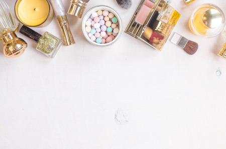 meteorites: Glamour chic cosmetic background in golden colour. Cosmetic objects frame with gold heels, gold glitter nail polish, perfume bottle, meteorites, blush, lip gloss, brushes.