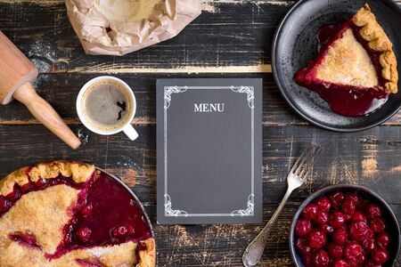 cherry pie: Baking background with sliced cherry pie, flour, rolling pin and menu chalkboard on the black wooden table. Ingredients for bakingdessert or pie making