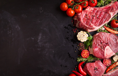 beef meat: Raw juicy meat steaks ready for roasting on a black chalk board background. Rib eye steak on the bone, veal shank (ossobuco), fillet with cherry tomatoes, hot pepper and herbs. Space for text