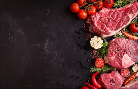 Raw saftiges Fleisch Steaks bereit für auf einem schwarzen Kreidetafel Hintergrund rösten. Rib-Eye-Steak auf dem Knochen, Kalbshaxe (ossobuco), Filet mit Kirschtomaten, Paprika und Kräutern. Platz für Text