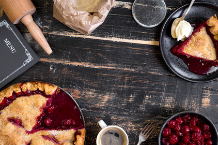 Homemade sliced cherry pie, bag with flour, rolling pin on the black wooden table. Baking background. Top view Stock Photo