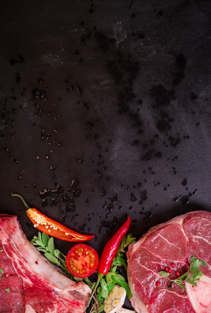 rib eye: Raw juicy meat steaks ready for roasting on a black chalk board background. Rib eye steak on the bone, veal shank (ossobuco), fillet with cherry tomatoes, hot pepper and herbs. Space for text