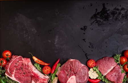 Prime bistecche di carne succosa pronto per la torrefazione su un gesso nero bordo sfondo. Bistecca con l'osso con l'osso, stinco di vitello (ossobuco), filetto con pomodorini, peperoncino ed erbe. Spazio per il testo