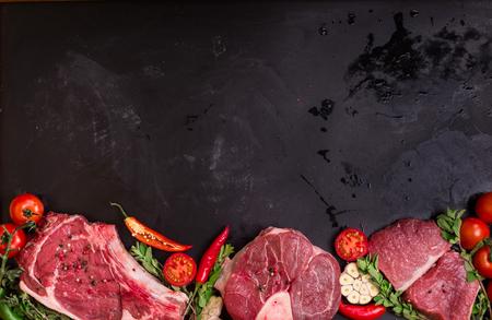 Raw steaks de viande prêts à rôtir sur une pierre noire board background. Entrecôte d'oeil sur l'os, jarret de veau (ossobuco), filet avec des tomates cerises, le piment et les herbes. Espace pour le texte Banque d'images - 52916689